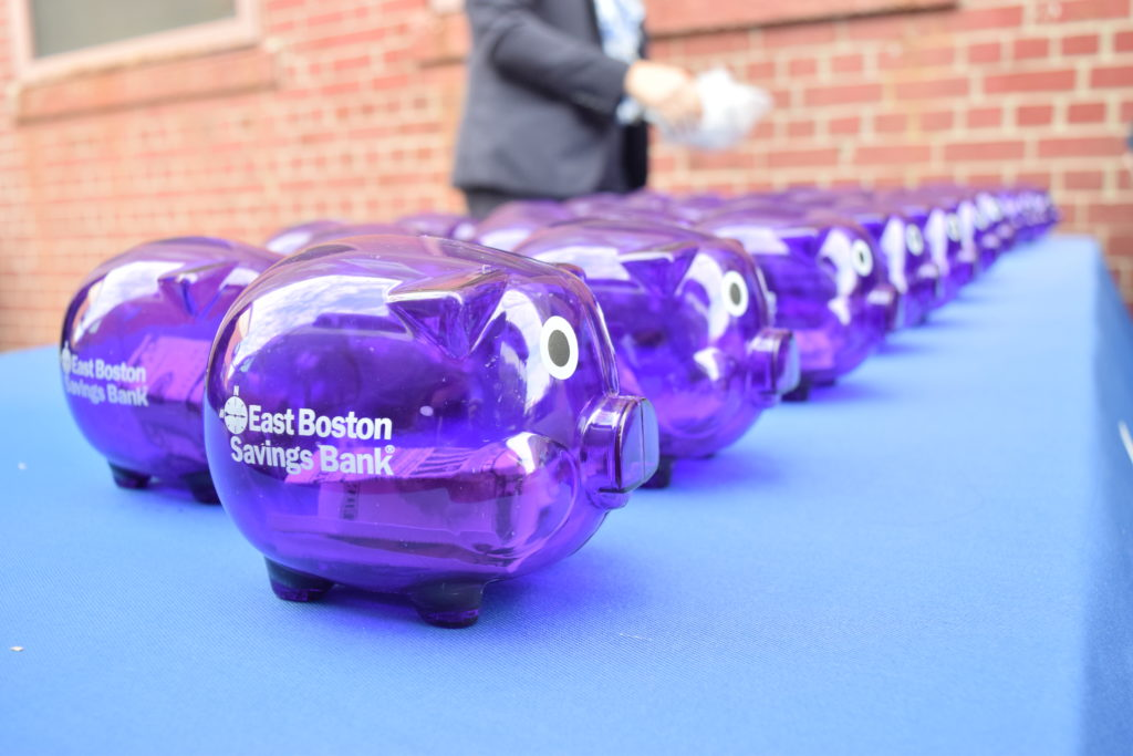 long row of purple plastic piggy banks on a table